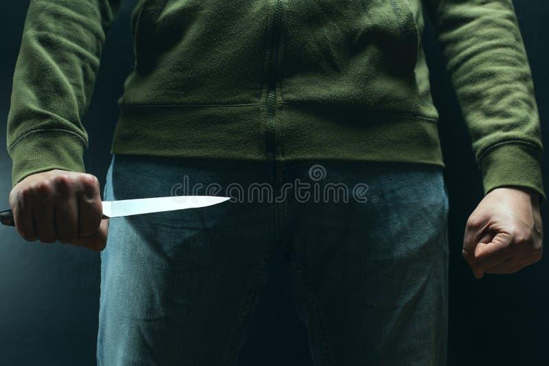 Ένας εγκληματίας με ένα όπλο μαχαιριών απειλεί να σκοτώσει Εγκληματικότητα, έγκλημα, κακοποιός ληστείας στοκ φωτογραφίες