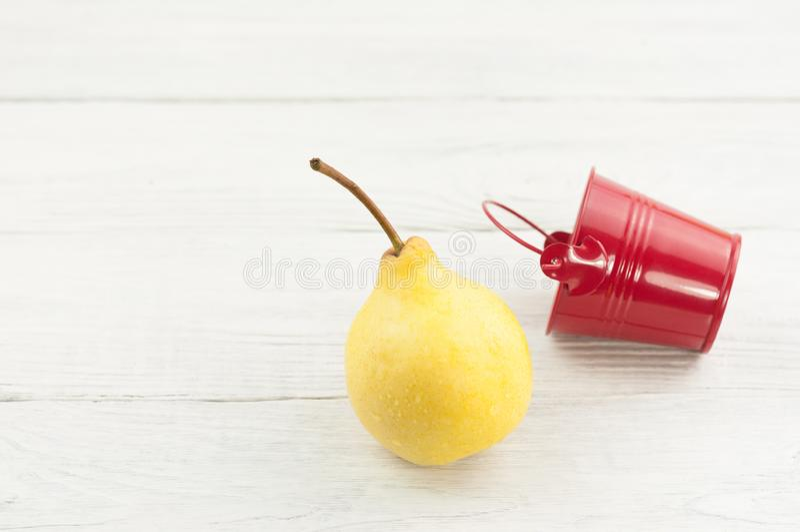 Ένας ενιαίος φρέσκος κίτρινος ώριμος ολόκληρος κάδος αχλαδιών και κενός κόκκινος μετάλλων ψεμάτων στοκ φωτογραφίες με δικαίωμα ελεύθερης χρήσης