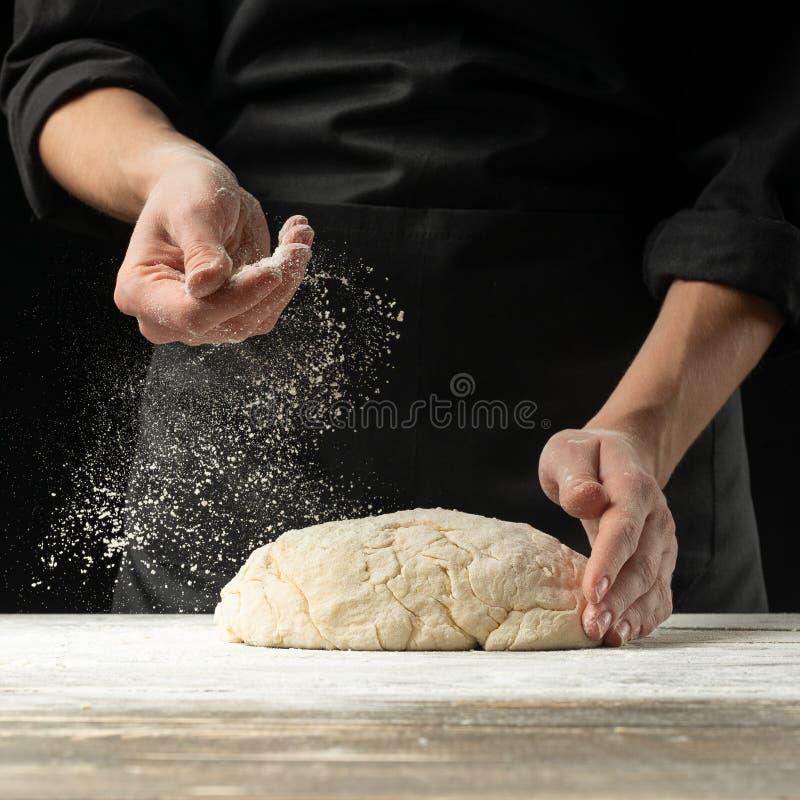 Ένας επαγγελματικός μάγειρας σε μια επαγγελματική κουζίνα προετοιμάζει τη ζύμη αλευριού για να κάνει τα βιο-ιταλικά ζυμαρικά έννο στοκ εικόνες