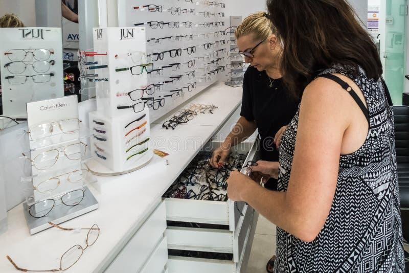 Ένας επαγγελματικός πωλητής βοηθά μια γυναίκα για να επιλέξει τα γυαλιά ανάγνωσης σε ένα οπτικομετρικό κατάστημα στην πόλη Nahari στοκ φωτογραφίες με δικαίωμα ελεύθερης χρήσης