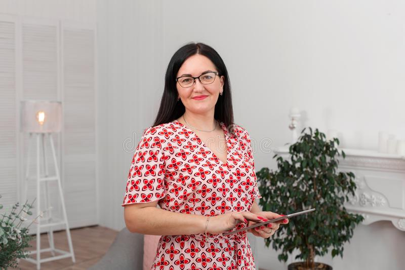 Ένας επαγγελματικός ψυχολόγος γιατρών με τα γυαλιά κάθεται σε ένα φωτεινό γραφείο με μια ταμπλέτα στα χέρια του και χαμογελά στη  στοκ εικόνες με δικαίωμα ελεύθερης χρήσης