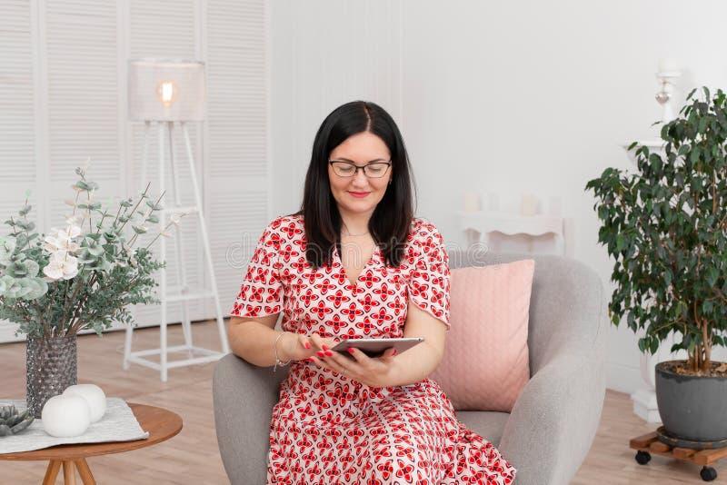 Ένας επαγγελματικός ψυχολόγος γιατρών με τα γυαλιά κάθεται σε ένα φωτεινό γραφείο με μια ταμπλέτα στα χέρια του και χαμογελά στη  στοκ φωτογραφία με δικαίωμα ελεύθερης χρήσης
