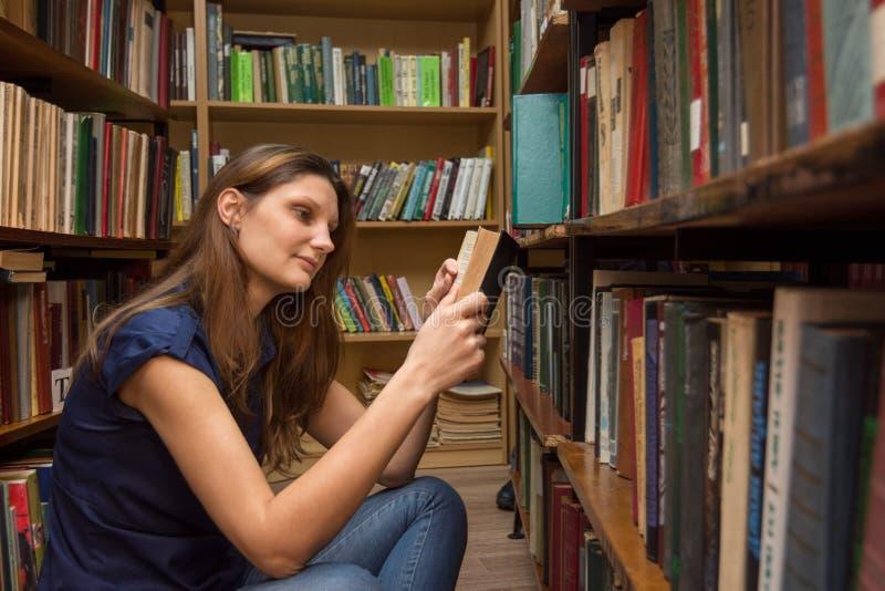 Ένας επισκέπτης βιβλιοθηκών διαβάζει ένα βιβλίο σκύβοντας στο πάτωμα μεταξύ των ραφιών στοκ εικόνες