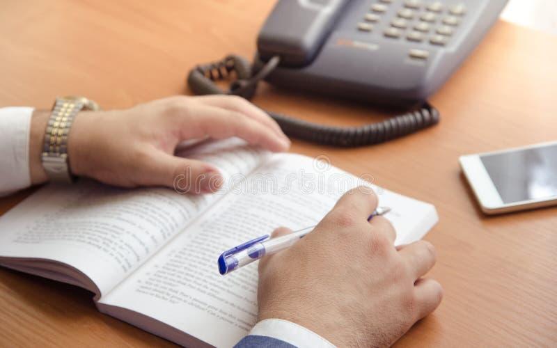 Ένας επιχειρηματίας κάνει τις σημειώσεις σε ένα επεκταθε'ν βιβλίο Στα χέρια πλαισίων μόνο στοκ φωτογραφία με δικαίωμα ελεύθερης χρήσης