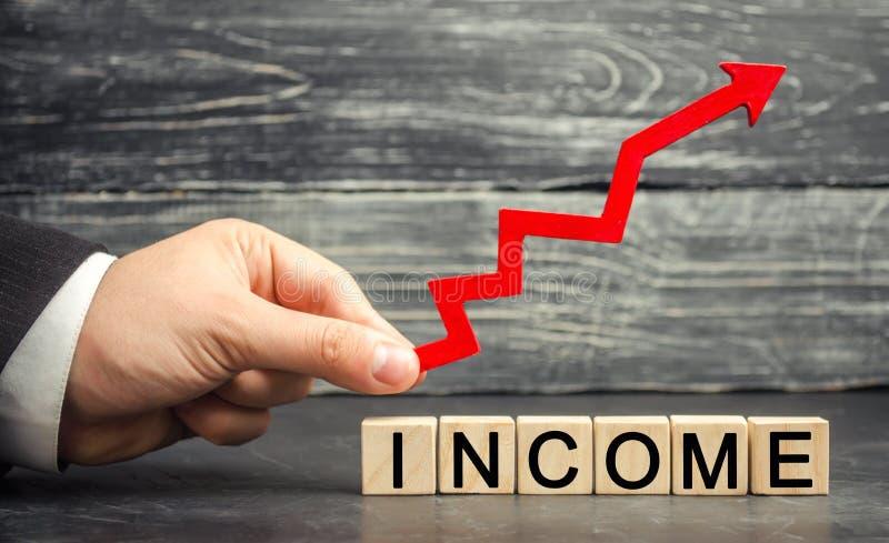 Ένας επιχειρηματίας κρατά ένα βέλος επάνω επάνω από το εισόδημα επιγραφής Έννοια της επιχειρησιακής επιτυχίας, της οικονομικής αύ στοκ φωτογραφίες με δικαίωμα ελεύθερης χρήσης