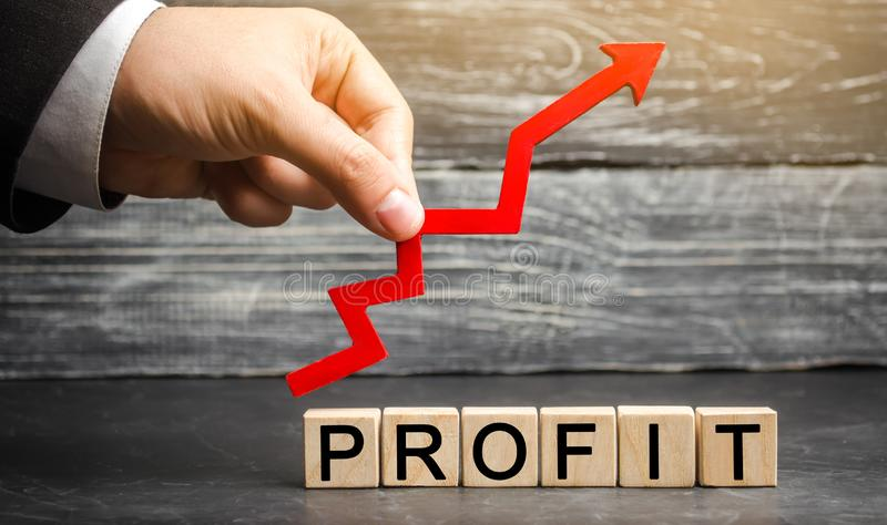 """Ένας επιχειρηματίας κρατά ένα κόκκινο επάνω στο βέλος και την επιγραφή """"κέρδος """" Έννοια της επιχειρησιακής επιτυχίας, της οικονομ στοκ εικόνα με δικαίωμα ελεύθερης χρήσης"""