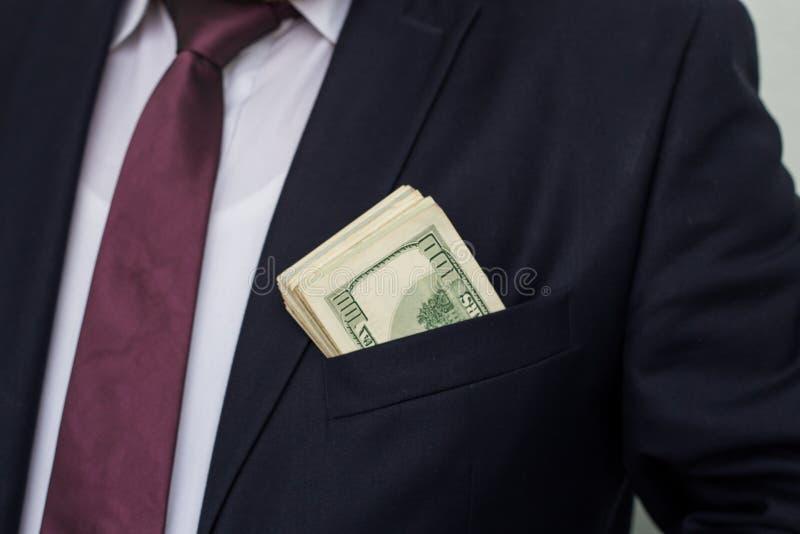 Ένας επιχειρηματίας παρουσιάζει ένα ποσό των μετρητών, τα βάζει στην τσέπη κοστουμιού του στοκ εικόνα με δικαίωμα ελεύθερης χρήσης