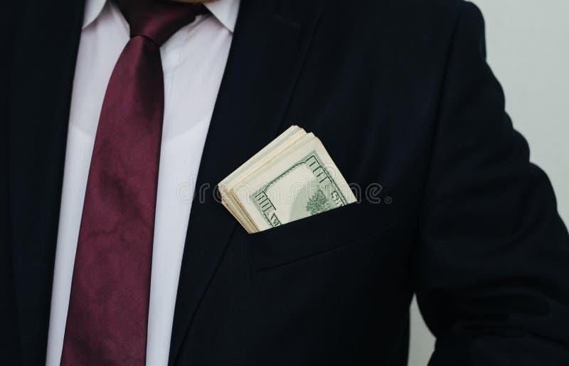 Ένας επιχειρηματίας παρουσιάζει ένα ποσό των μετρητών, τα βάζει στην τσέπη κοστουμιού του στοκ εικόνα
