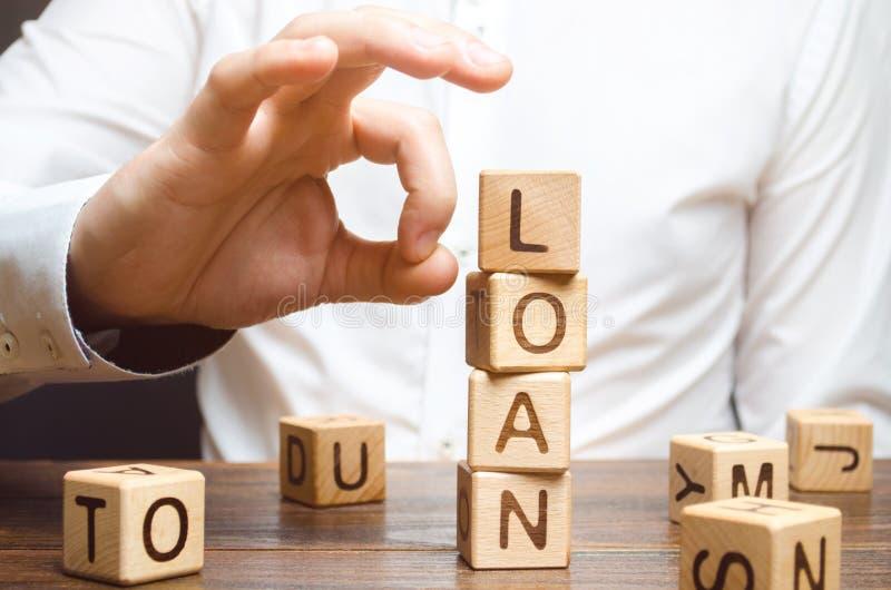 Ένας επιχειρηματίας προσπαθεί να πάρει κάτω από έναν πύργο των κύβων με το δάνειο λέξης άρνηση να πληρωθούν τα δάνεια Απλοποίηση  στοκ φωτογραφίες με δικαίωμα ελεύθερης χρήσης