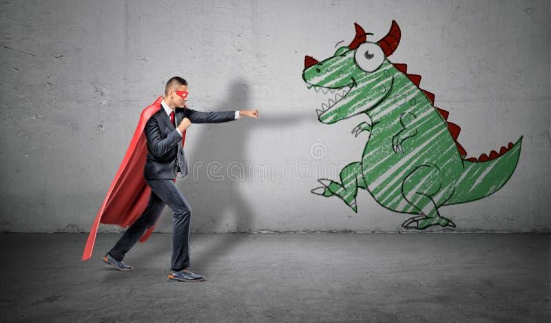 Ένας επιχειρηματίας σε ένα κόκκινο ακρωτήριο που στέκεται στην πάλη θέτει έτοιμο να παλεψει μια εικόνα ενός δράκου στον κοντινότε στοκ εικόνες