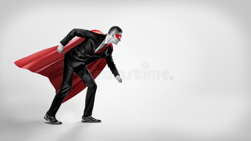 Ένας επιχειρηματίας σε ένα κόκκινο ακρωτήριο superhero και μια μάσκα που στέκονται στη θέση αρχικών γραμμών στο γκρίζο υπόβαθρο στοκ φωτογραφίες με δικαίωμα ελεύθερης χρήσης