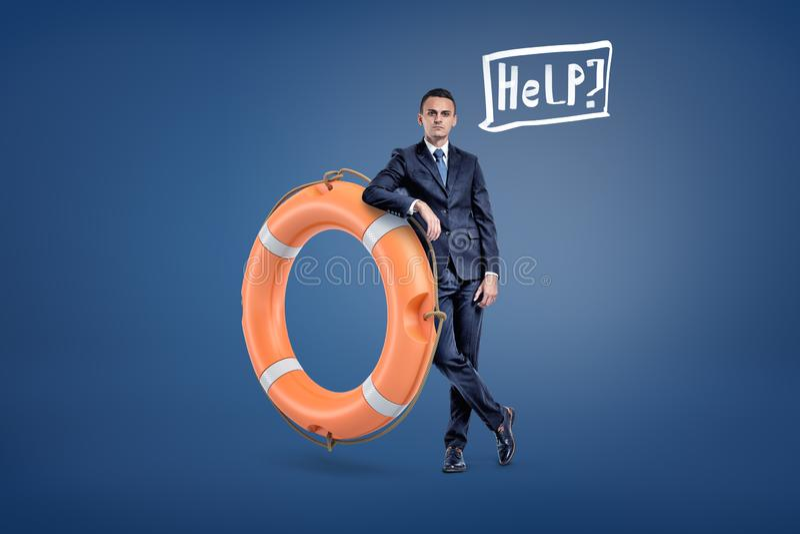 Ένας επιχειρηματίας στέκεται σε έναν μεγάλο πορτοκαλή σημαντήρα ζωής με μια λεκτική φυσαλίδα κρατώντας μια βοήθεια λέξης μέσα στοκ εικόνες