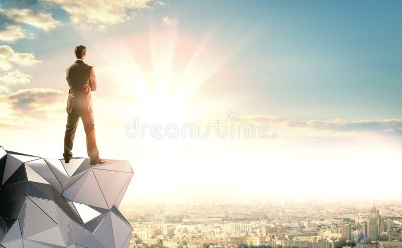 Ένας επιχειρηματίας στέκεται σε μια αφηρημένη κατασκευή στοκ εικόνες