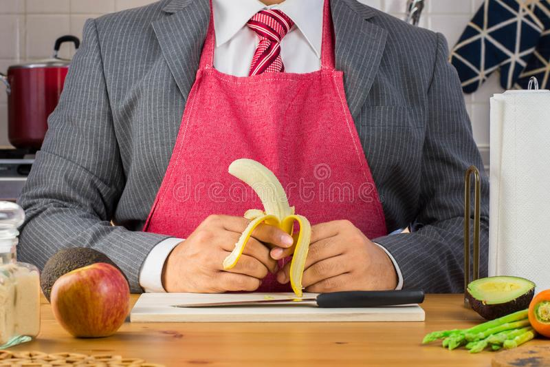 Ένας επιχειρηματίας στο κοστούμι και τον κόκκινο δεσμό που φορούν την ποδιά και που κρατούν μια μικρή ξεφλουδισμένη μπανάνα στην  στοκ εικόνα
