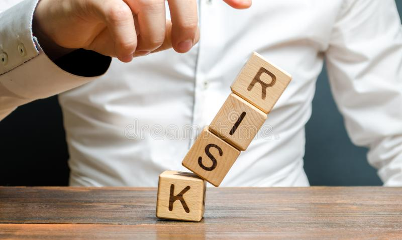 Ένας επιχειρηματίας χτυπά κάτω έναν πύργο των κύβων με τον κίνδυνο λέξης Διαχείρηση κινδύνων, αξιολόγηση των δαπανών, επιχείρηση  στοκ εικόνα