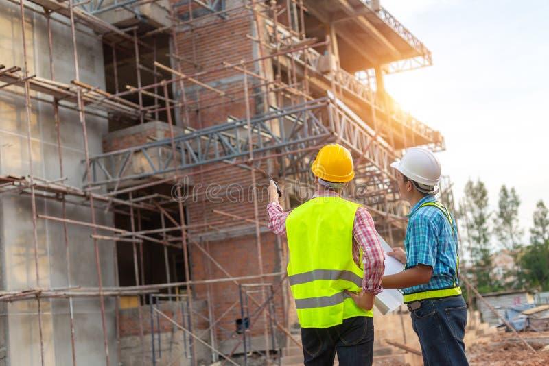 Ένας εργάτης οικοδομών ελέγχει μια χύνοντας συγκεκριμένη αντλία στο constru στοκ εικόνα