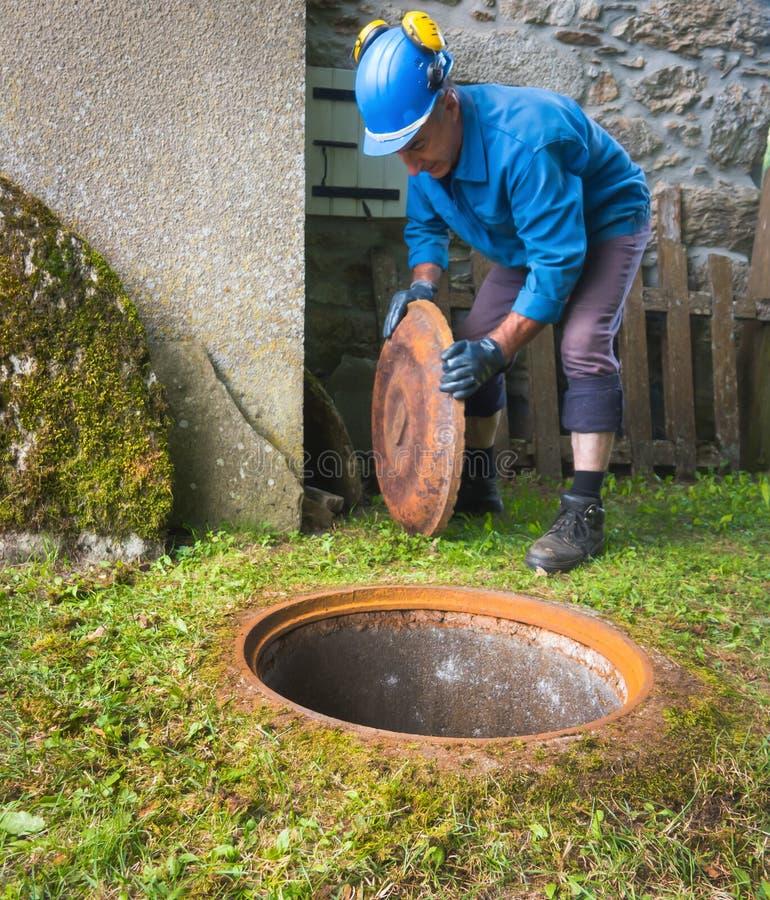 Ένας εργαζόμενος ανοίγει μια καταπακτή για να κατεβεί μέσα υπόγεια στοκ εικόνες