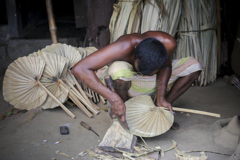 Ένας εργαζόμενος είναι πολυάσχολος στην παραγωγή του χεριού - κρατημένος ανεμιστήρας στοκ φωτογραφία με δικαίωμα ελεύθερης χρήσης