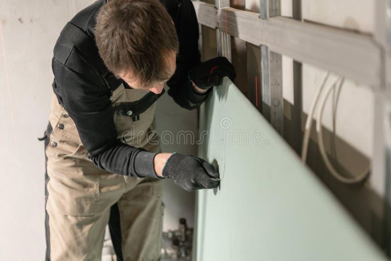 Ένας εργαζόμενος οικοδόμος ατόμων κάνει έναν χαρακτηρισμό στον ξηρό τοίχο για την ηλεκτρική καλωδίωση Κατασκευή ξηρών τοίχων μετά στοκ φωτογραφία με δικαίωμα ελεύθερης χρήσης