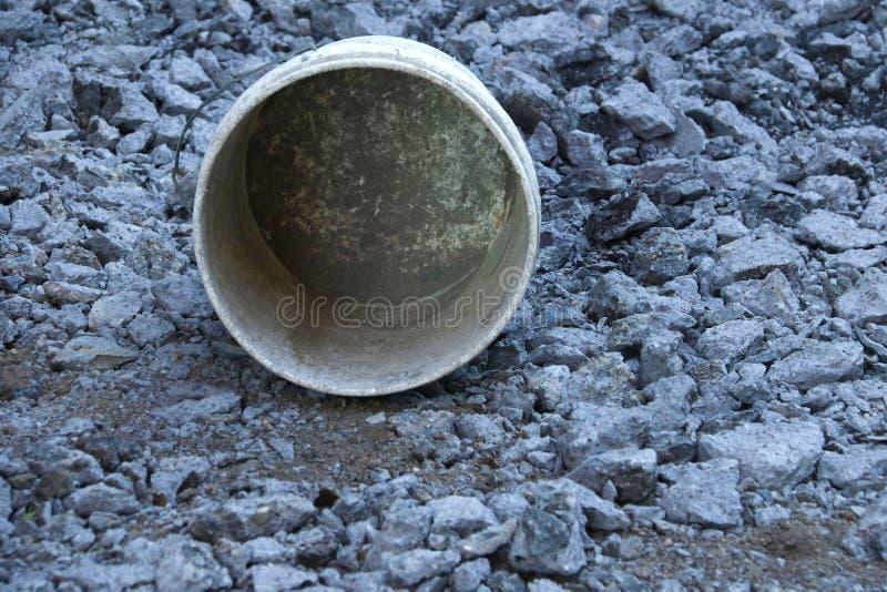 Ένας λερωμένος άσπρος κάδος στους γκρίζους βράχους και το ρύπο στοκ εικόνα με δικαίωμα ελεύθερης χρήσης