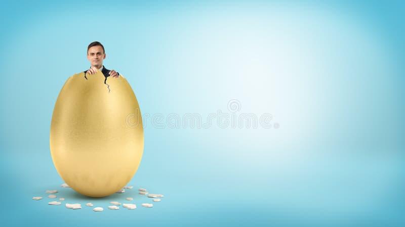 Ένας ευτυχής επιχειρηματίας κοιτάζει από μέσα από ένα γιγαντιαίο χρυσό αυγό με μια σπασμένη κορυφή στοκ φωτογραφία με δικαίωμα ελεύθερης χρήσης
