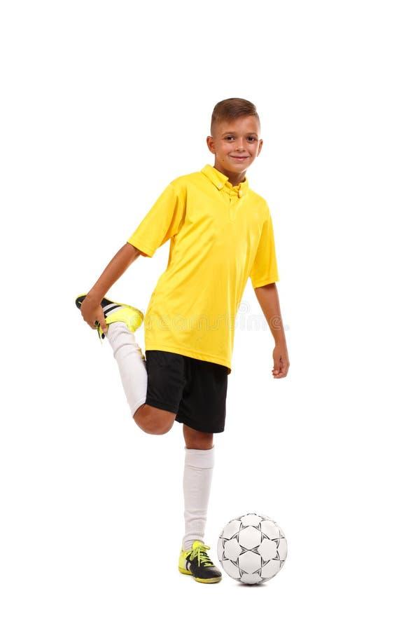 Ένας ευτυχής ποδοσφαιριστής θερμαίνει Ένα εύθυμο παιδί σε ένα ποδόσφαιρο ομοιόμορφο που απομονώνει σε ένα άσπρο υπόβαθρο Αθλητική στοκ φωτογραφία με δικαίωμα ελεύθερης χρήσης