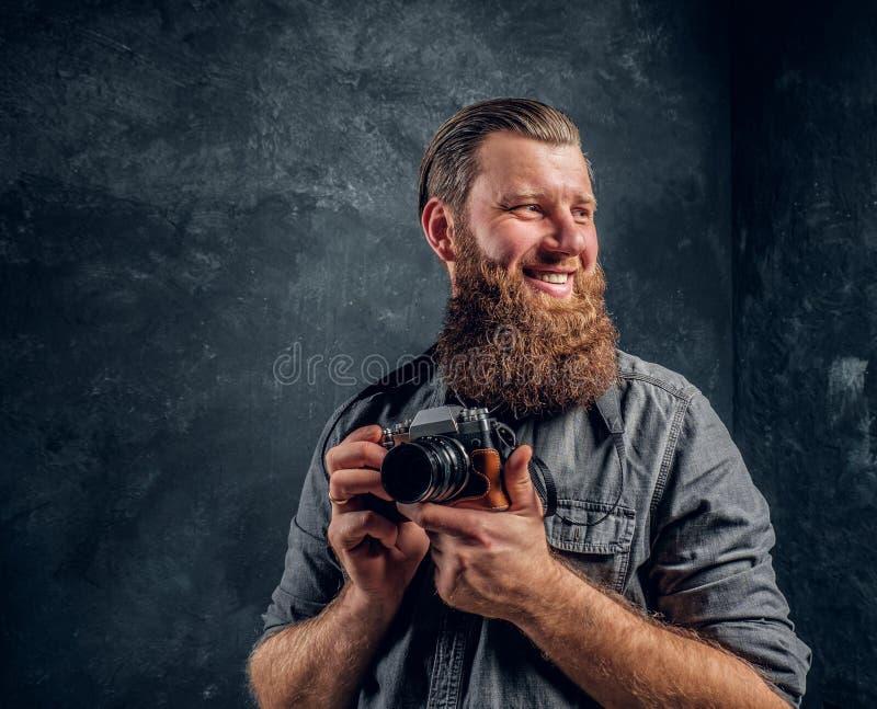 Ένας εύθυμος γενειοφόρος φωτογράφος που φορά μια γκρίζα εκμετάλλευση μια κάμερα φωτογραφιών και που εξετάζει μια κάμερα στοκ φωτογραφία με δικαίωμα ελεύθερης χρήσης