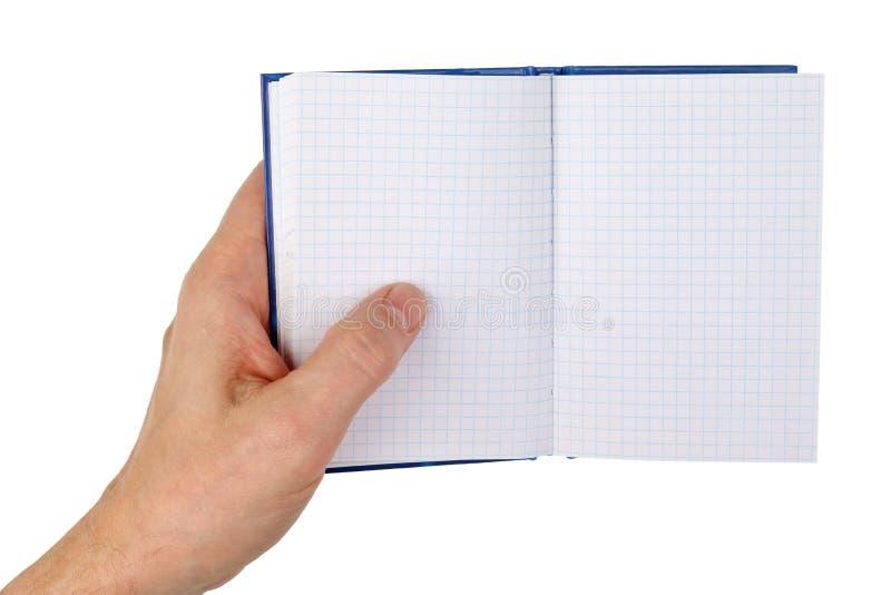 Ένας ηληκιωμένος κρατά στο χέρι του ένα ανοικτό σημειωματάριο με κενό που ελέγχεται στοκ φωτογραφία με δικαίωμα ελεύθερης χρήσης