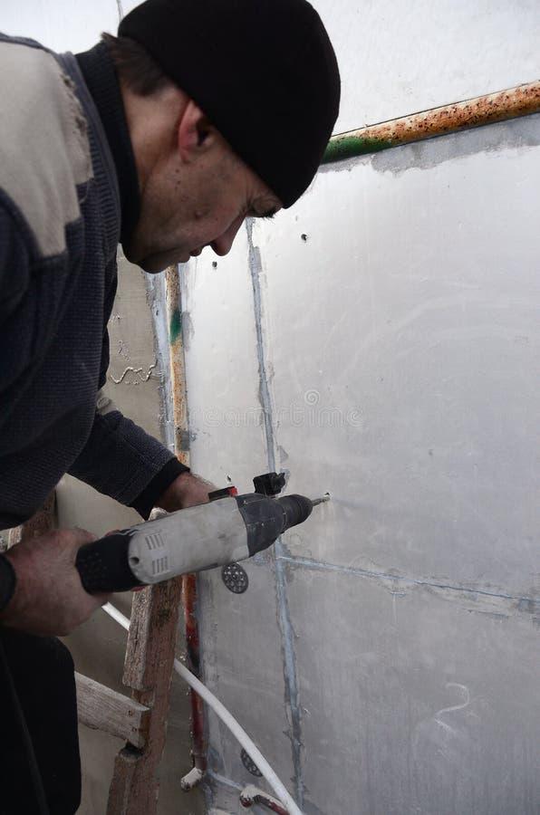 Ένας ηλικιωμένος εργάτης τρυπά μια τρύπα σε έναν styrofoam τοίχο για την επόμενη εγκατάσταση ενός πλαστικού γόμφου ενίσχυσης με τ στοκ εικόνες με δικαίωμα ελεύθερης χρήσης