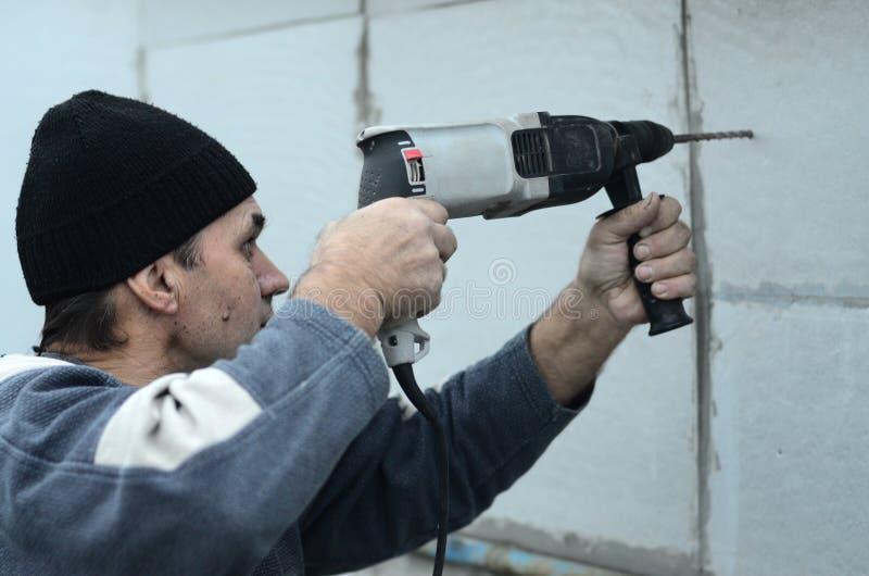 Ένας ηλικιωμένος εργάτης τρυπά μια τρύπα σε έναν styrofoam τοίχο για την επόμενη εγκατάσταση ενός πλαστικού γόμφου ενίσχυσης με τ στοκ φωτογραφία με δικαίωμα ελεύθερης χρήσης