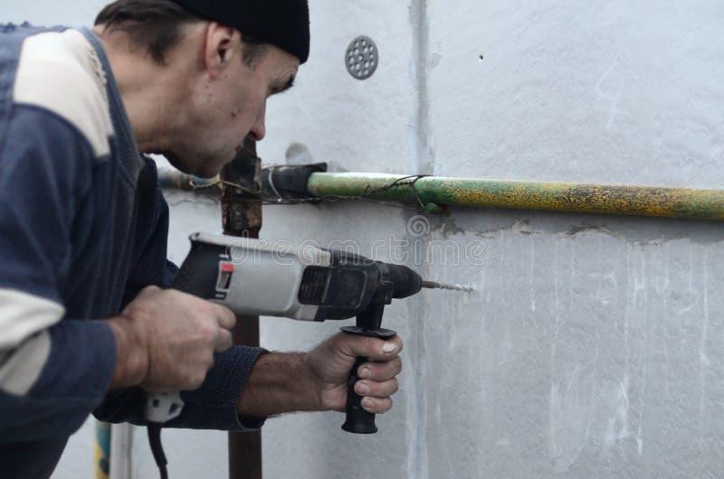 Ένας ηλικιωμένος εργάτης τρυπά μια τρύπα σε έναν styrofoam τοίχο για την επόμενη εγκατάσταση ενός πλαστικού γόμφου ενίσχυσης με τ στοκ εικόνα