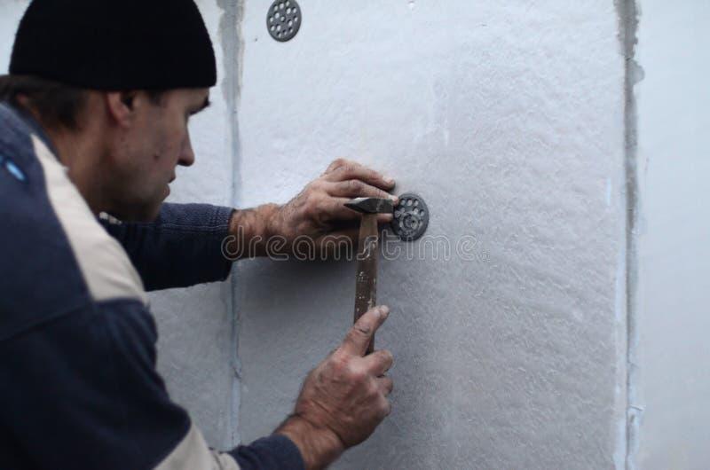 Ένας ηλικιωμένος εργάτης φράζει έναν γόμφο σε μια πλαστική ομπρέλα τοποθετεί σε έναν styrofoam τοίχο στοκ εικόνα με δικαίωμα ελεύθερης χρήσης