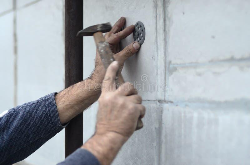 Ένας ηλικιωμένος εργάτης φράζει έναν γόμφο σε μια πλαστική ομπρέλα τοποθετεί σε έναν styrofoam τοίχο στοκ φωτογραφία