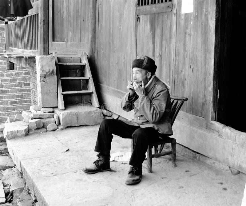 Ένας ηλικιωμένος χωρικός που απολαμβάνει τις ώρες απογεύματός του που παίζουν τη φυσαρμόνικα έξω από το σπίτι του στοκ φωτογραφία με δικαίωμα ελεύθερης χρήσης