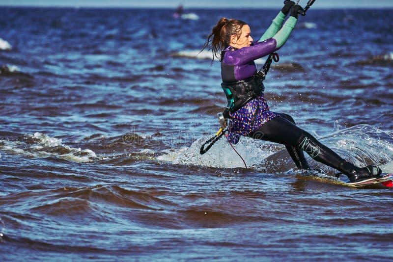 Ένας θηλυκός kiter γλιστρά στην επιφάνεια του νερού Παφλασμοί της μύγας νερού χώρια στοκ φωτογραφία με δικαίωμα ελεύθερης χρήσης