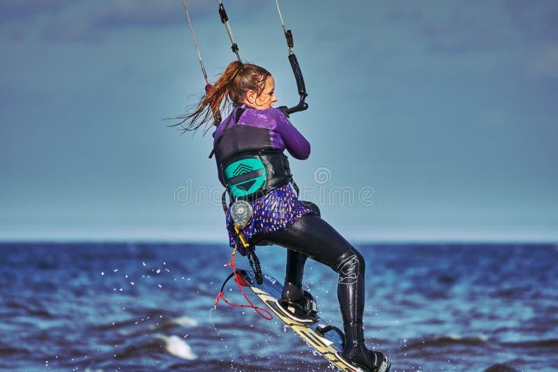 Ένας θηλυκός kiter πηδά πέρα από μια μεγάλη λίμνη στοκ εικόνες με δικαίωμα ελεύθερης χρήσης