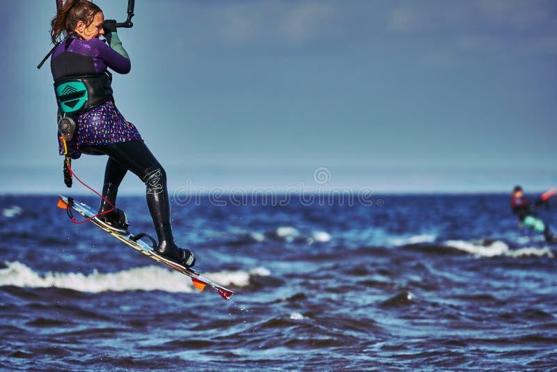 Ένας θηλυκός kiter πηδά πέρα από μια μεγάλη λίμνη στοκ φωτογραφία με δικαίωμα ελεύθερης χρήσης