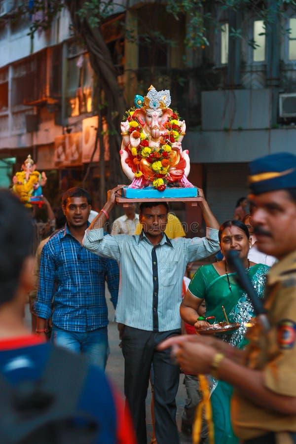 Ένας θιασώτης που φέρνει το είδωλο του Λόρδου Ganesha για τη βύθιση στοκ φωτογραφία