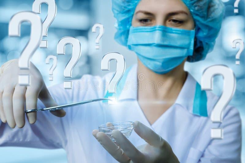 Ένας ιατρικός εργαζόμενος στο σφιγκτήρα που κρατά το ερωτηματικό στοκ φωτογραφία