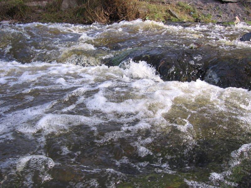 Ένας ισχυρός, οργισμένος χείμαρρος νερού στον ποταμό, ο αφρός που πλημμυρίζει την άνοιξη στα κύματα στοκ φωτογραφίες με δικαίωμα ελεύθερης χρήσης