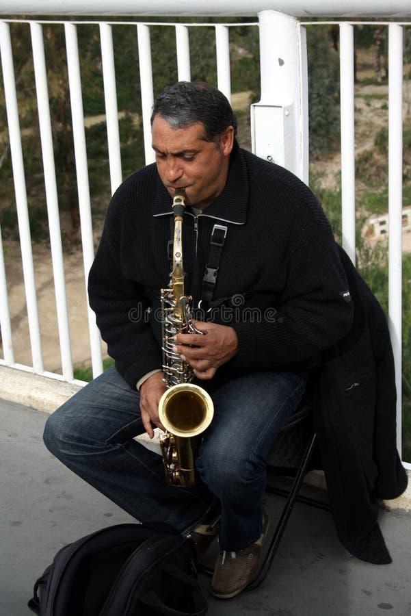 Ένας καλλιτέχνης οδών παίζει ένα saxophone Είναι saxophonist που κάθεται στοκ εικόνα με δικαίωμα ελεύθερης χρήσης