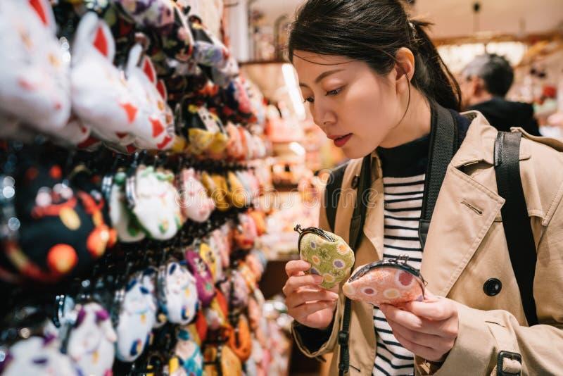 Ένας καλός θηλυκός τουρίστας που επιλέγει τα πορτοφόλια νομισμάτων στοκ εικόνα με δικαίωμα ελεύθερης χρήσης