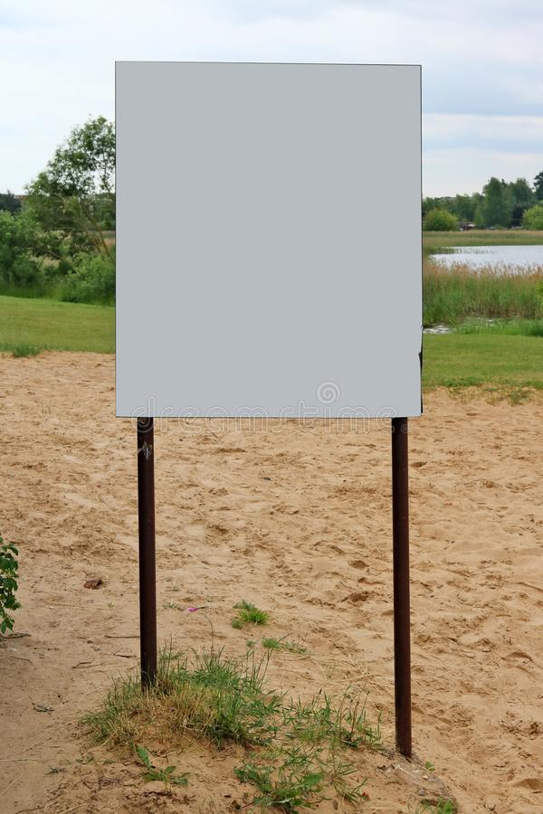 Ένας κενός πίνακας πληροφοριών εγκαθίσταται σε μια αμμώδη παραλία κοντά στο θόριο στοκ φωτογραφία
