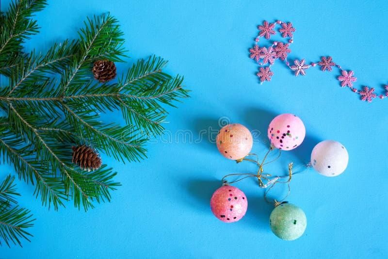 Ένας κλάδος ενός χριστουγεννιάτικου δέντρου, snowflakes, των κώνων και των ζωηρόχρωμων σφαιρών σε ένα μπλε υπόβαθρο αναμονή διακο στοκ εικόνα
