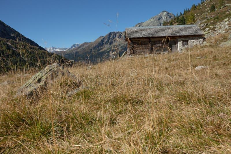 Ένας κλειστός σταύλος στην πτώση μπροστά από ένα λιβάδι βουνών στοκ εικόνα