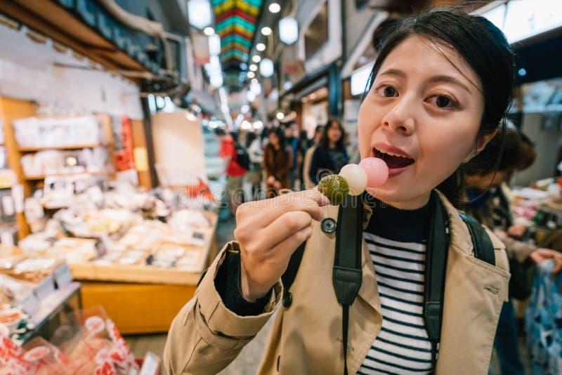 Ένας κομψός θηλυκός ταξιδιώτης που τρώει Dango στοκ φωτογραφίες