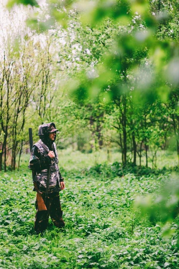 Ένας κυνηγός ατόμων περιπλανιέται με ένα πυροβόλο όπλο στο βροχερό καιρό μέσω ενός δάσους άνοιξη στοκ φωτογραφία με δικαίωμα ελεύθερης χρήσης