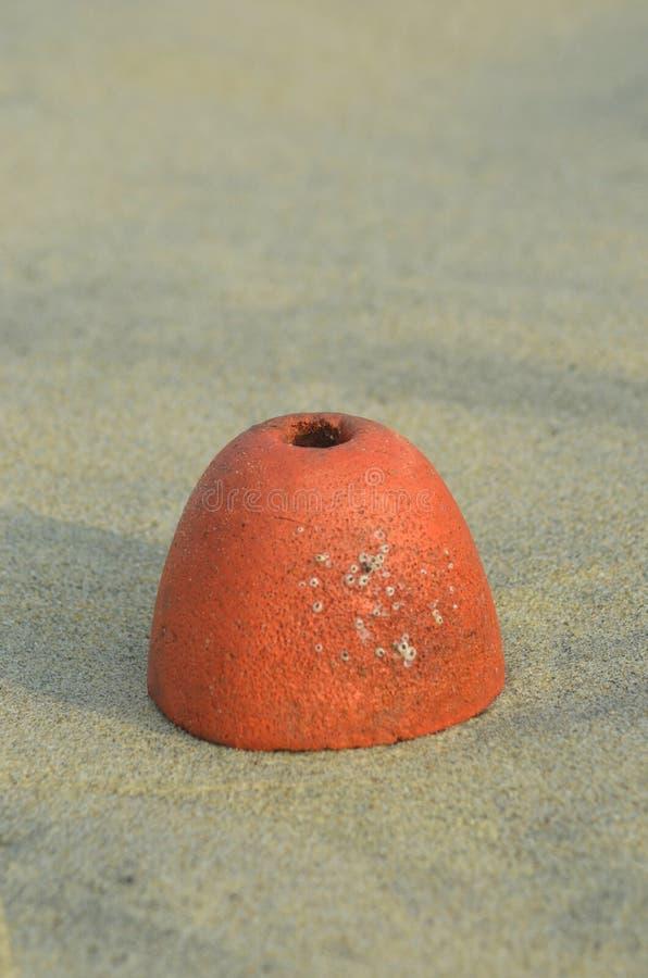 Ένας κωνικός πορτοκαλής σημαντήρας που στηρίζεται στην άμμο στοκ φωτογραφία με δικαίωμα ελεύθερης χρήσης