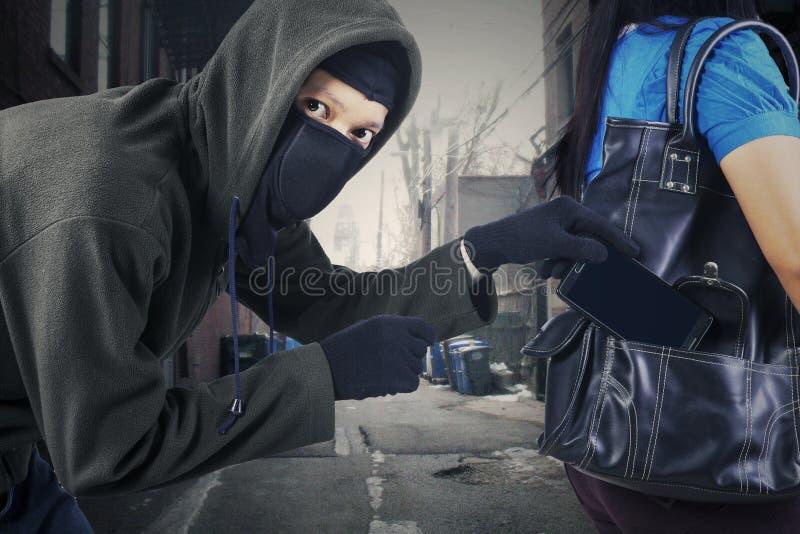 Ένας κλέφτης που κλέβει το κινητό τηλέφωνο στοκ φωτογραφίες με δικαίωμα ελεύθερης χρήσης