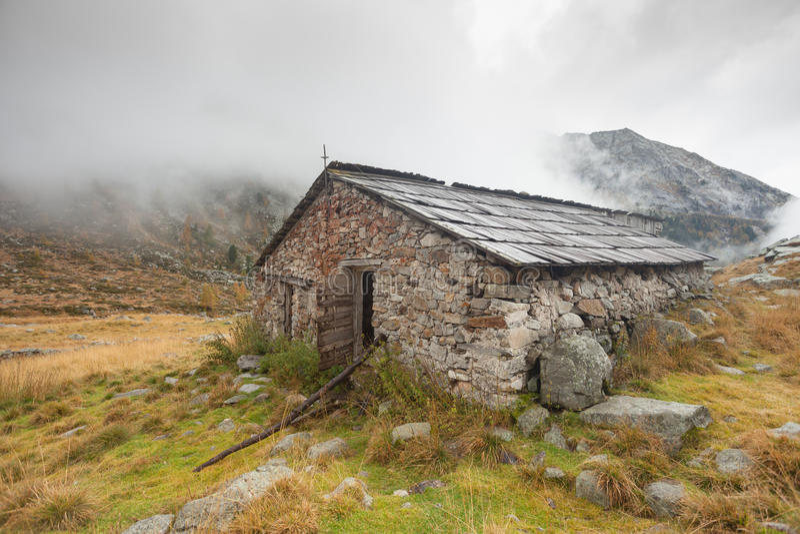 Ένας κλειστός σταύλος στην πτώση μπροστά από ένα λιβάδι βουνών στοκ εικόνα με δικαίωμα ελεύθερης χρήσης